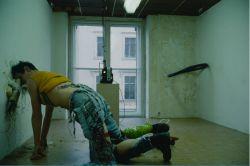 """Bildunterschrift: Der Künstler John Bock bei der Performance innerhalb seines Werks """"LiquiditätsAuraAromaPortfolio"""" während der Berlin Biennale 1998"""